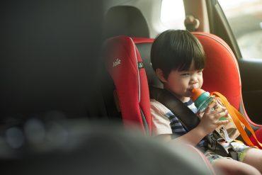 Little boy drinking in a car seat